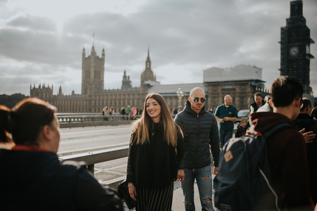 LONDON, ENGLAND - 25th October, 2018: Happy couple walking by Westminster Bridge sidewalk, with Westminster Palace and Big Ben in the background, in London, England.
