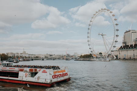 LONDON, ENGLAND - 25th October, 2018: A Citycruises touristic boat navigating by Thames river with a lot of tourists on it, with London Eye in the background, in London, England.
