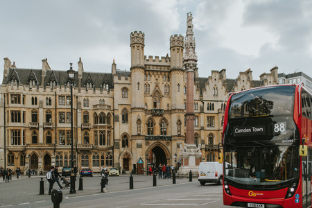 LONDON, ENGLAND - 25th October, 2018: Westminster square and a typical red bus crossing the scene, in London, England