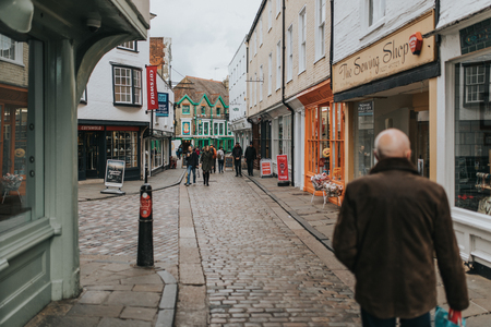 CANTERBURY, ENGLAND - October 28th, 2018: Pedestrian walking along cobblestoned street, with shops around it, and traditional architecture in the village of Canterbury, Kent, England.