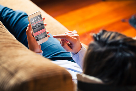 Woman holding a mobile phone to visit a travel agency website while lies down at home.