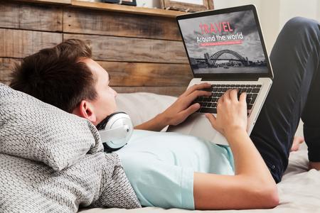 Hombre visitando el sitio web de una agencia de viajes por Internet con una computadora portátil, mientras está acostado en la cama en su casa.