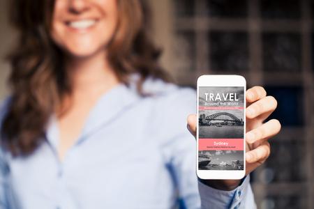 Glimlachende vrouw met een mobiele telefoon met reisnieuwswebsite in het scherm.