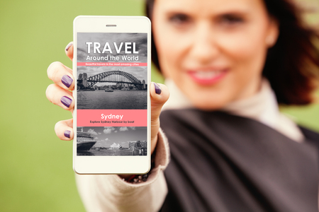 Woman showing mobile phone with travel news website in the screen.