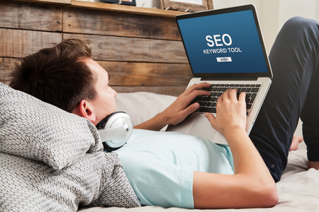 Man doing SEO keyword positioning with a laptop at home.