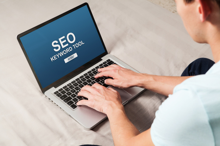 Mężczyzna robi pozycjonowanie SEO na stronie internetowej za pomocą laptopa. Zdjęcie Seryjne