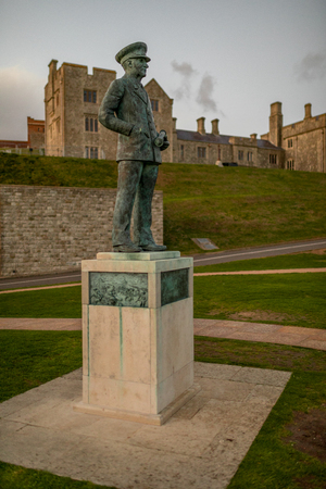 Admiral Sir Bertram Ramsay statue, in front of Dover Castle attached building, during sunset, in Dover, Kent, United Kingdom.