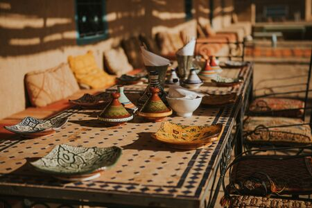 Moroccan meal table settings with ceramic tajines and dishes.