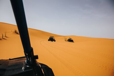 Off road buggys crossing dunes in the desert. Rally raid adventure.