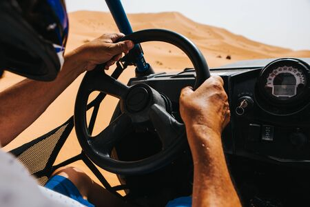 Man hands driving a buggy in the desert dunes. View from the cockpit.