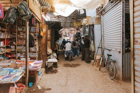 Rissani, Morocco - September 18th, 2019: People walking along a corridor inside the Rissani bazaar market in Morocco. Editorial