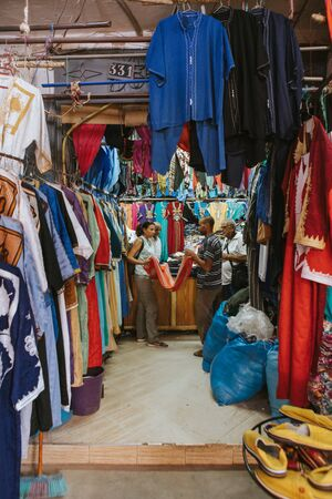 Rissani, Morocco - September 18th, 2019: Textile shop and man and woman talking about clothes prices in Rissani bazaar market, in Morocco.