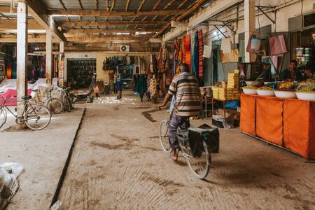 Rissani, Morocco - September 18th, 2019: Man crossing a corridor by bicycle in Risanni bazaar market in Morocco. Editorial