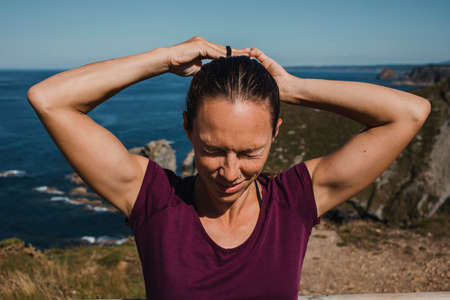 Athletic woman making herself a ponytail in the hair, with the coastline in the background