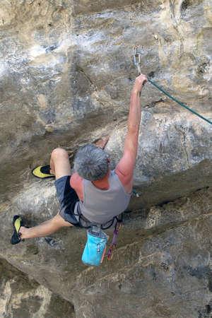 limestone:  man reaches for clip climing limestone thailand