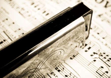 tarnished: old harmonica on sheet music )retro inpired image ) Stock Photo
