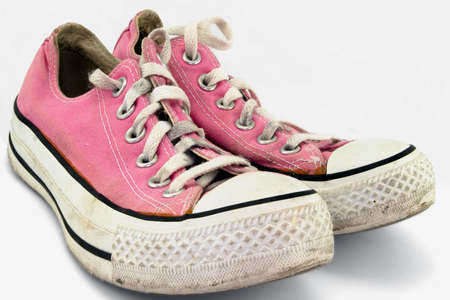 converse: A pair of old sneakers, isolated on white background. Stock Photo