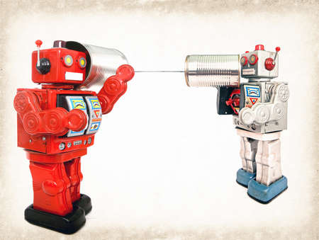 two retro robots talk on tin can phones 免版税图像