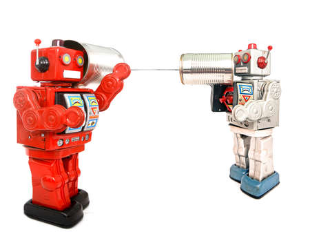 two retro robots talk on tin can phones Foto de archivo