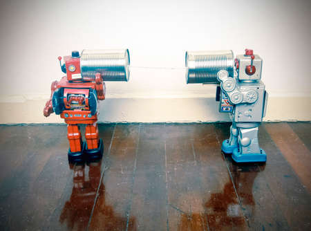 Two retro  Robots toys talking on tin can phones on an old wooden floor Stock fotó - 91318942