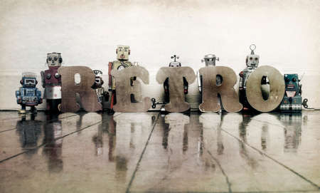 the word RETRO tit wooden letters with retro robot toys on an old wooden floor
