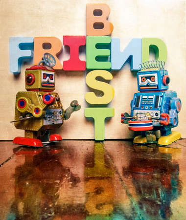 BEST FRIEND word with wooden letters and two retro robot toys on an old wooden floor with reflection
