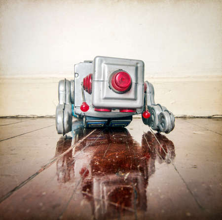 Over worked retro silver robot face down on old wooden floor with reflection Stock Photo