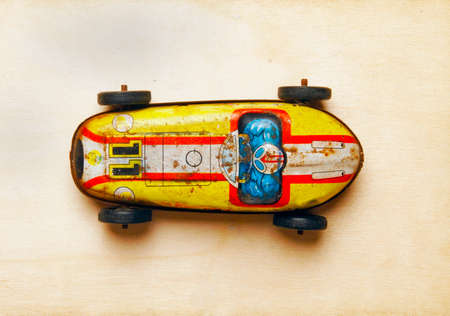 old tin toy  car on a wood background shot from above