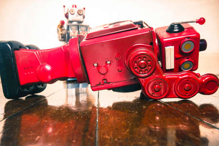 shot down concept with retro tobot toys on a wooden floor with reflection Stock Photo