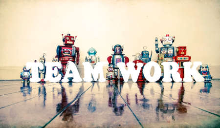 Retro robots spell out TEAM WORK   with reflectiona toned co;or image  Banco de Imagens
