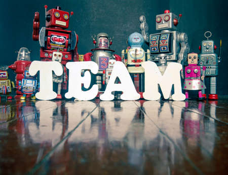 Retro robots spell out TEAM WORK   with reflectiona toned co;or image  Stock Photo