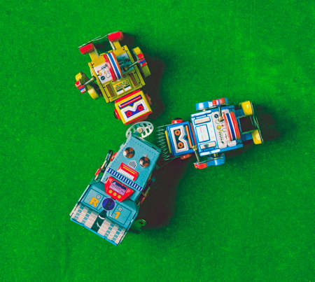 three retro robots lookung up to the sky on toy grass