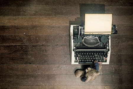 an old teddy bear at on a vintage typewriter from above  on a wooden floor  Stock Photo