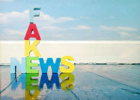 Fack News ,wooden letters on old wooden floor with reflection Stock Photo