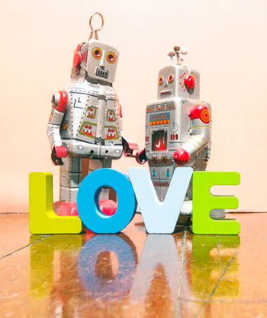 I LOVE U  with wooden letters on old wooden floor with two retro robot toys Stock Photo