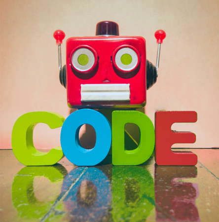 retro red robot head and the word CODE on a old wooden floor 写真素材