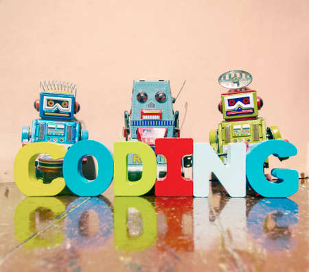 レトロなロボットのおもちゃで古い木製の床にウィット木製の文字をコーディングする単語