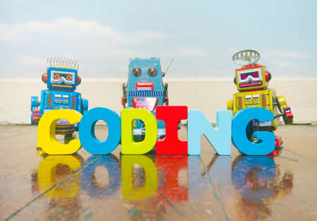 the word coding wit wooden letters on a old wooden floor with retro robot toys 스톡 콘텐츠