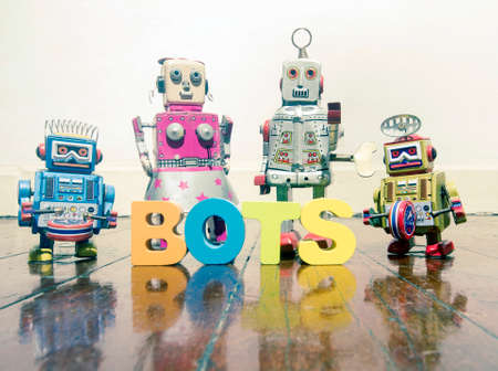 four retro robot toys and the word BOTS on a wooden floor Stock fotó