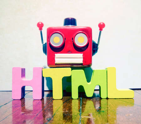 red retro robot head on the word  HTML on old wooden flor