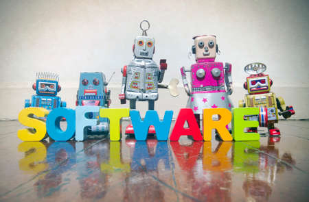 the word SOFTWARE made wit wooden letters  and robot toys on a wooden floor with copy space