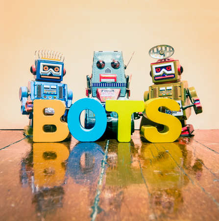 three retro robot toys and the word BOTS on a wooden floor