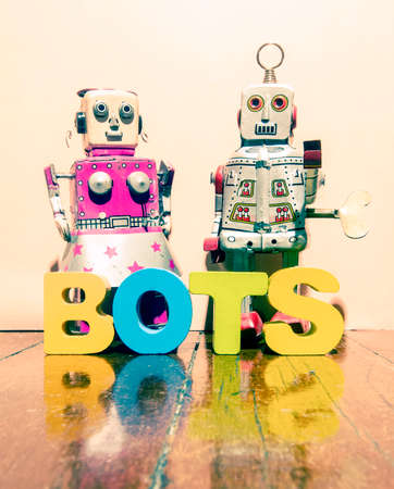 two retro robot toys and the word BOTS on a wooden floor Stock fotó - 93760231