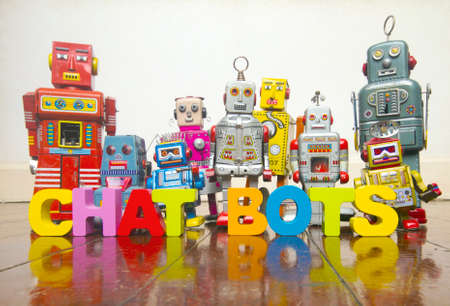 the word A CHAT BOTS  with wooden letters and retro toy robots  on an old wooden floor with reflection