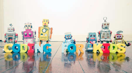 the words CODING FOR KIDS  with rtro robot toys on a wooden floor with reflection 写真素材 - 102900295