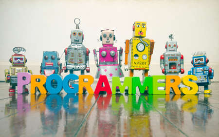 the word  PROGRAMMERS with wooden letters and retro toy robots  on an old wooden floor with reflection Stock fotó - 102900297