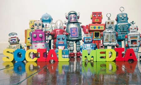 the words SOCIAL MEDIA   with retro robot toys on a wooden floor with reflection