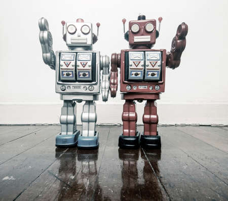 two vintage robots say hi  on a wooden floor toned image