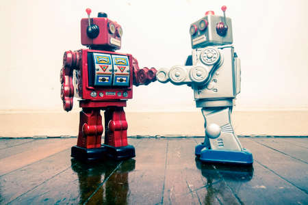 two vintage robot shake hands on a old wooden floor  toned image Stock fotó - 104587070