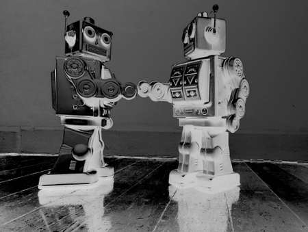 two vintage robot shake hands on a old wooden floor  solarized monochrome image